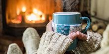person sitting in front of fire with wool socks and a hot mug