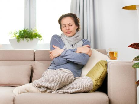woman sitting on a couch looking cold