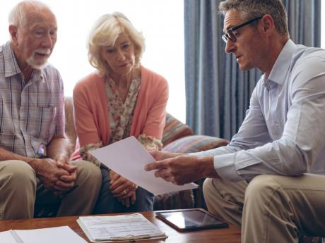 older couple going over report with man in their home