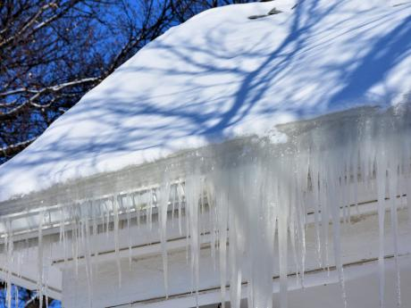 ice dam collecting on edge of snowy roof