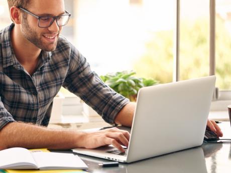 man happy at home looking at laptop