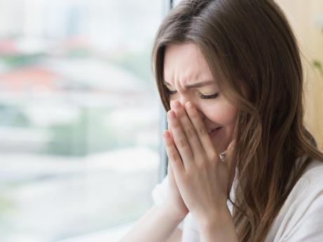 woman sneezing at home