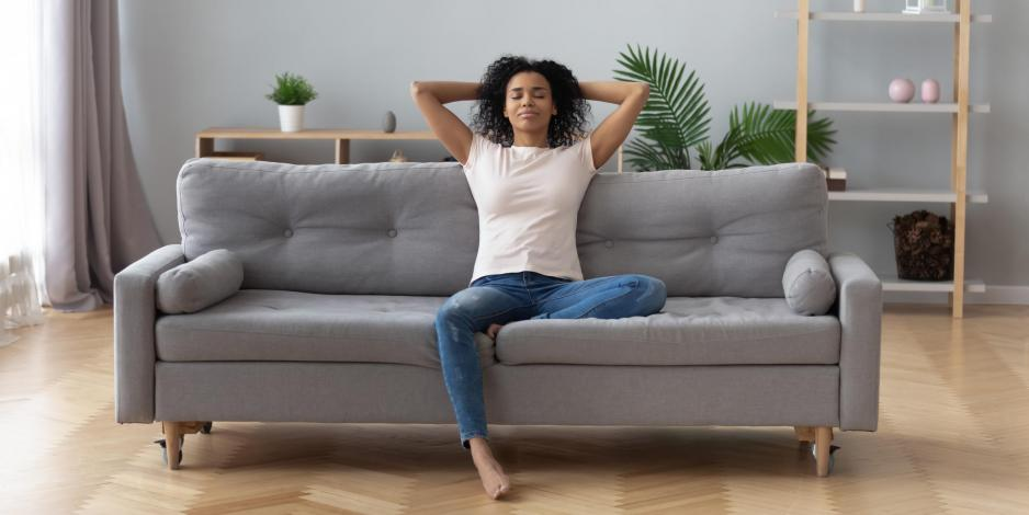 healthy woman sitting on a couch in a clean house