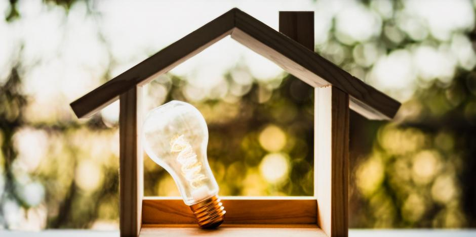 wooden hollow house with lightbulb inside with sun and leaves in background