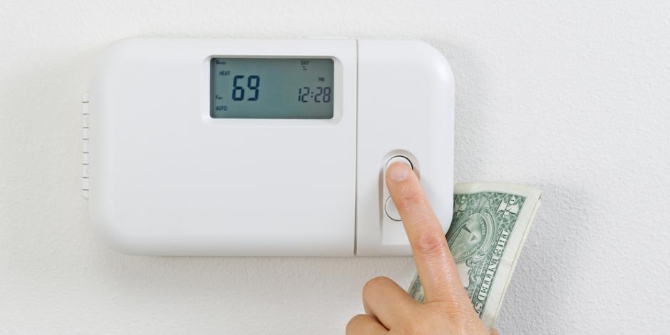 adjusting thermostat with money in hand, increasing utility bill concept
