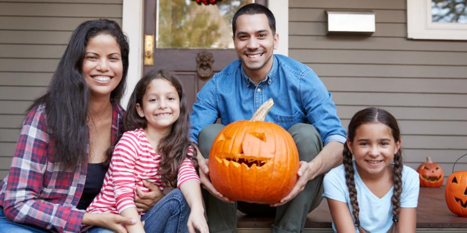 family on front porch holding a pumpkin