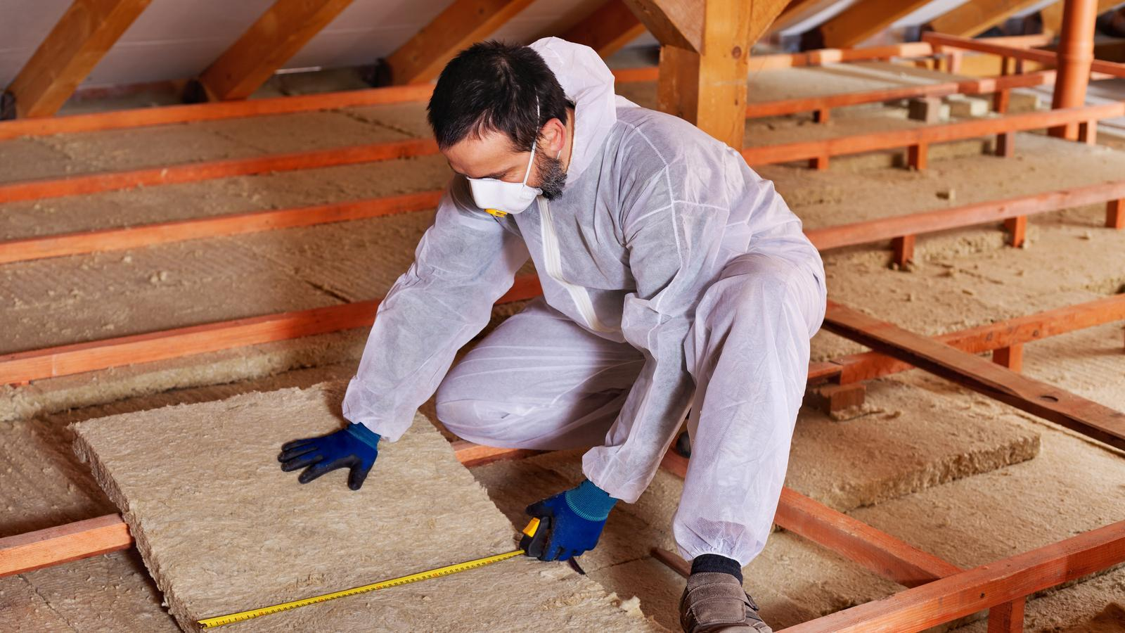 Contractor Measuring and Installing Insulation